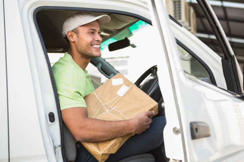 Smiling delivery driver in his van holding parcel iStock_000057474544_Small