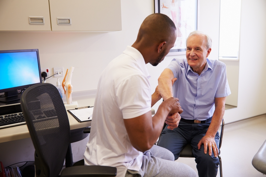 Senior Male Patient Working With Physiotherapist In Hospital